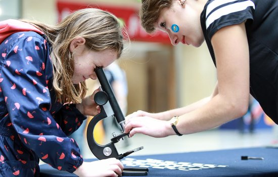 A young girl looks through a microscope at a Pi: Platform for Investigation event