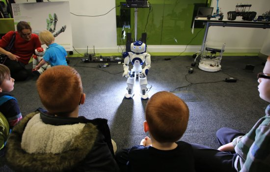 Children sat on the floor looking at a small white robot