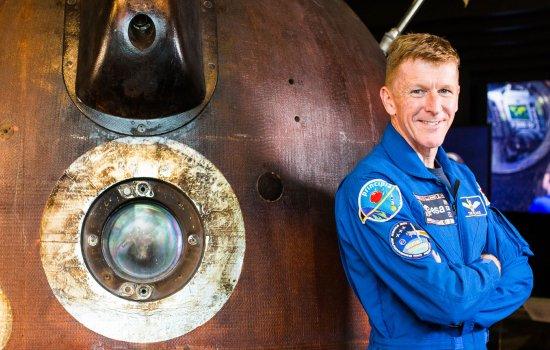 Tim Peake stood next to the Soyuz capsule
