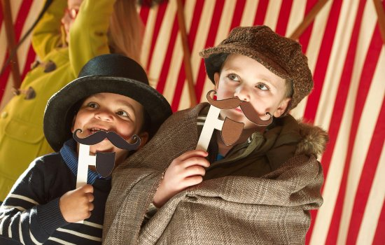 Two boys wearing Victorian hats and fake moustaches