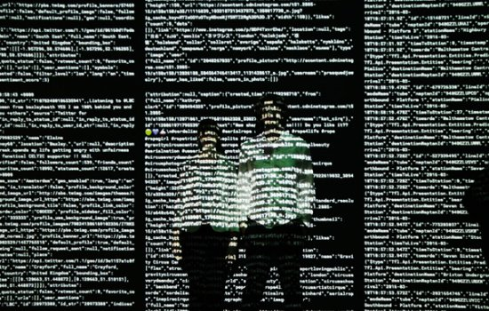 Tekja artist duo stood in front a wall of computer code