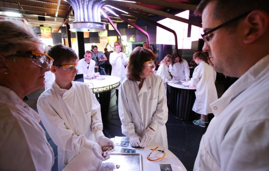 People in lab coats at a Pi event at MSI