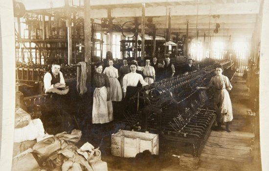 People operating Jacquard Looms to weave the fabric made from a mixture of cotton and wool.