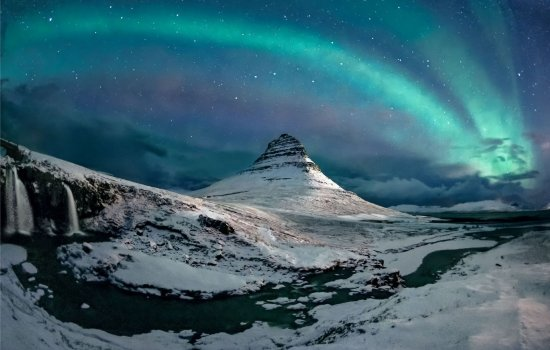 The aurora borealis above a snow-covered mountain