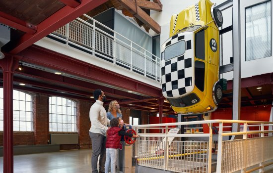 A young family looking at a Mini car suspended in the air