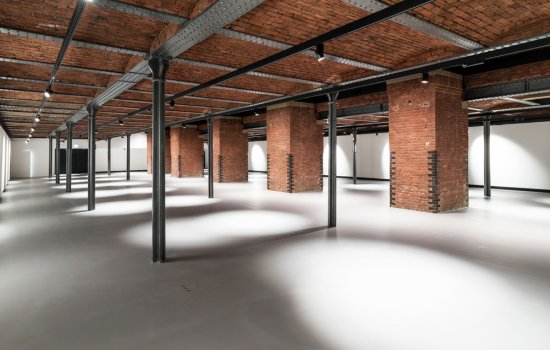 An empty new gallery space in a museum, with a brick ceiling and iron girders and pillars