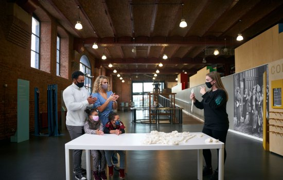 A young family and a museum explainer stood by a table in a museum gallery
