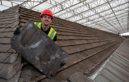 Person in hard hat on a roof, holding a large roof tile