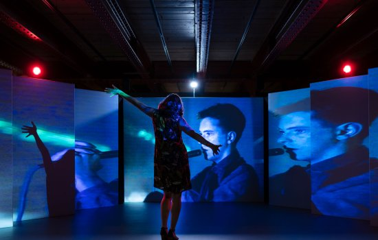 A woman stood in a dark room facing several screens