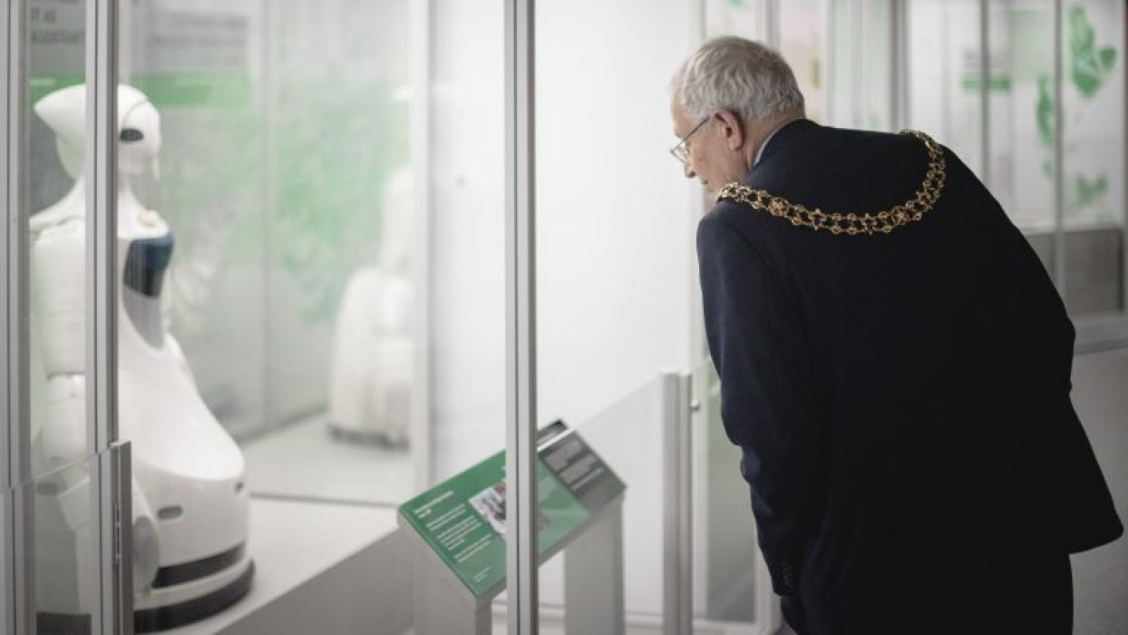 A man wearing a mayoral chain looking at a robot on display in a museum