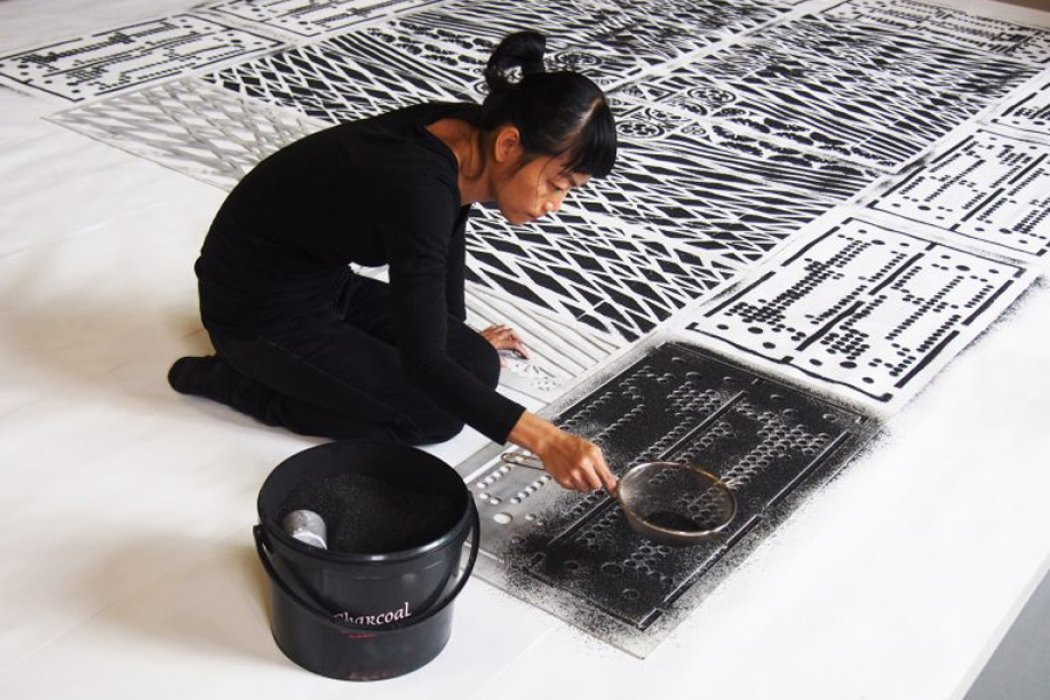 A woman drawing a pattern in charcoal on a white canvas