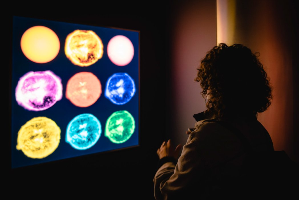 A woman stood in front of a screen depicting the sun at nine different wavelengths