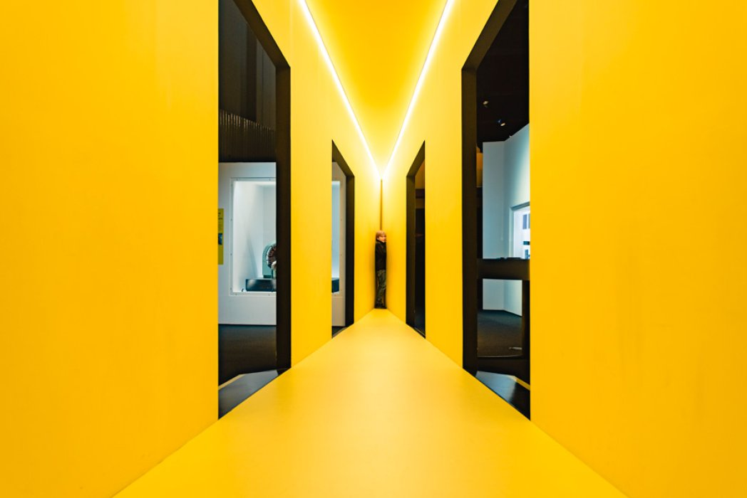 A brightly lit yellow corridor with two boys hiding at one end