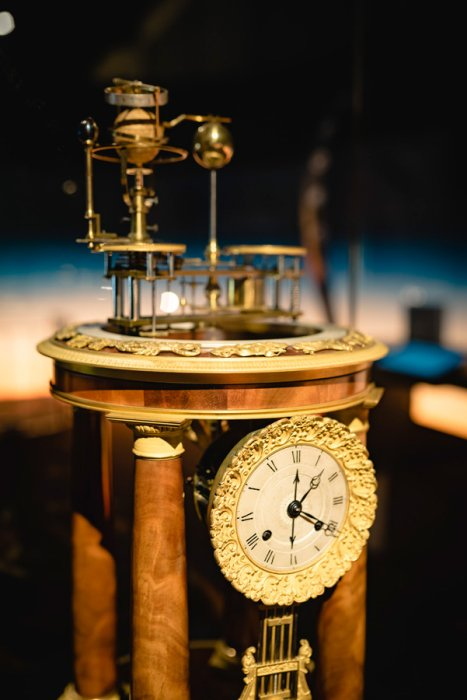 An ornate 19th century clock with an orrery on top of it