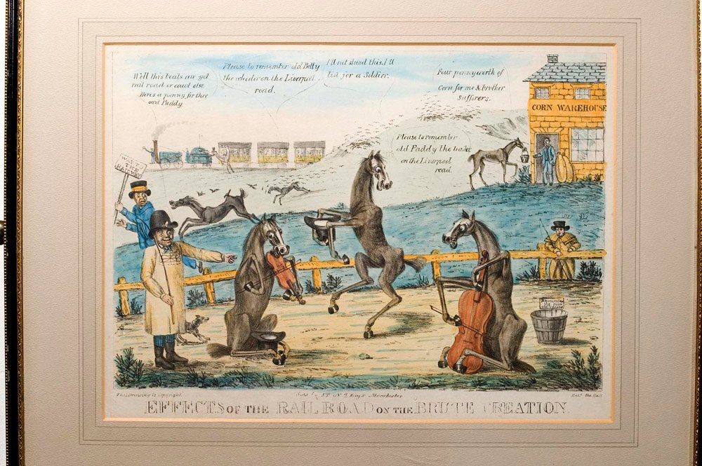Satirical print showing horses made redundant by the advent of the railway; in foreground three horses playing as street musicians, with passing train receiving a hind kick from indignant horse in background.