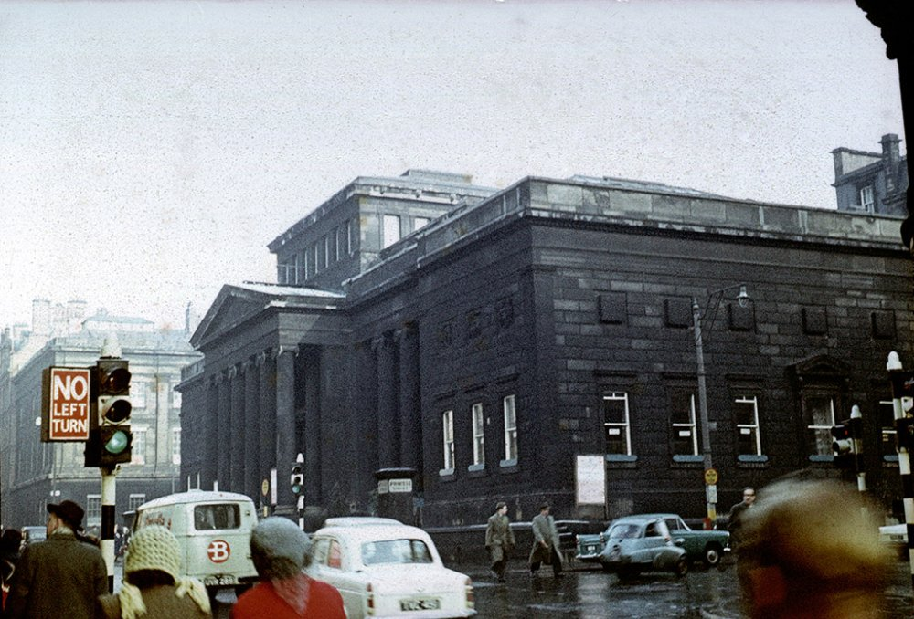 A large building blackened by coal soot, with car traffic and pedestrians passing by